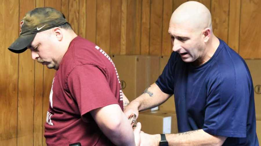 Youngstown police Capt. Kevin Mercer, right, demonstrates handcuffing techniques recently with Officer Dave Garcia during a training session for new hires at the Youngstown Police Department. Garcia is one of seven new hires at the department.