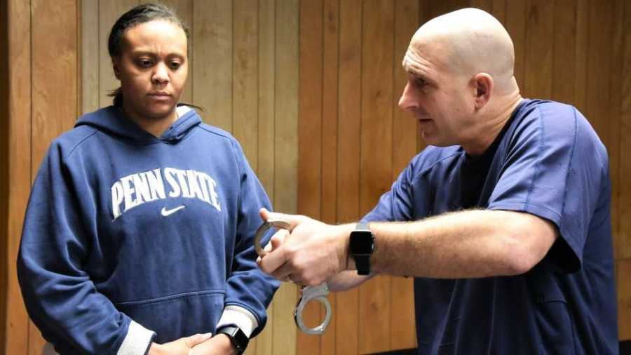 Youngstown police Lt. Kevin Mercer, right, displays a pair of handcuffs during a training session recently for seven new officers hired earlier this month. One of those officers, Tyra Grant, looks on in the background.