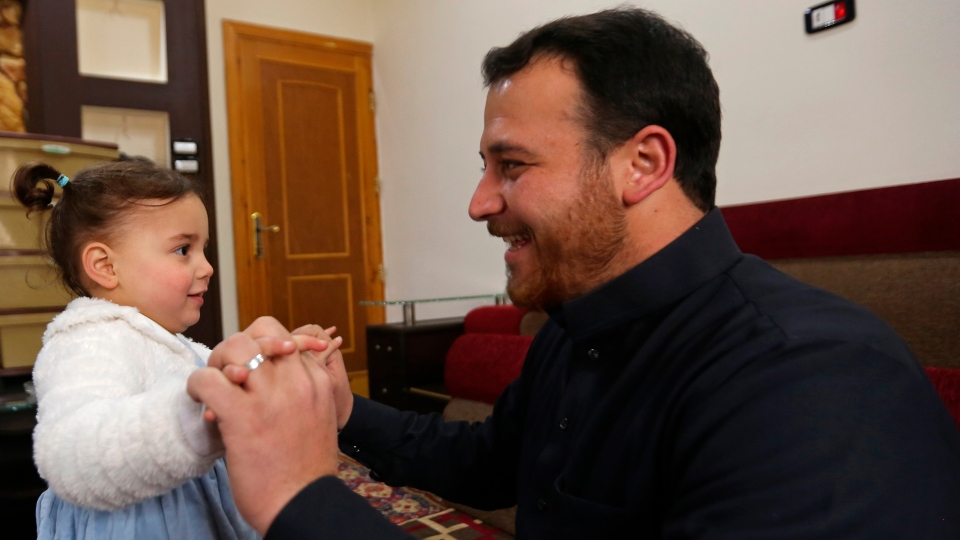 Abdullah Mohammed and his daughter, Salwa, laugh as bombs fall in Syria