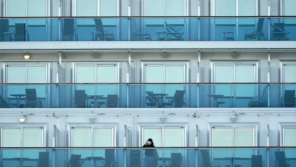A passenger stands on the balcony of the cruise ship Diamond Princess anchored at the Yokohama Port, near Tokyo Thursday, Feb. 6, 2020. Health workers said 10 more people from the Diamond Princess were confirmed ill with the virus, in addition to 10 others who tested positive on Wednesday. They were dropped off as the ship docked and transferred to nearby hospitals for further test and treatment.
