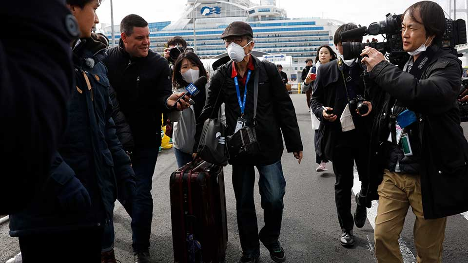 An unidentified passenger is surrounded by the media after he disembarked from the quarantined Diamond Princess cruise ship Wednesday, Feb. 19, 2020, in Yokohama, near Tokyo. Passengers tested negative for COVID-19 started disembarking Wednesday