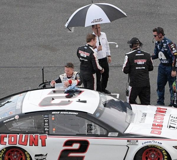 Brad Keselowski stands under an umbrella on pit road as rain forces a red flag during the NASCAR Daytona 500 auto race at Daytona International Speedway, Sunday, Feb. 16, 2020, in Daytona Beach, Fla.