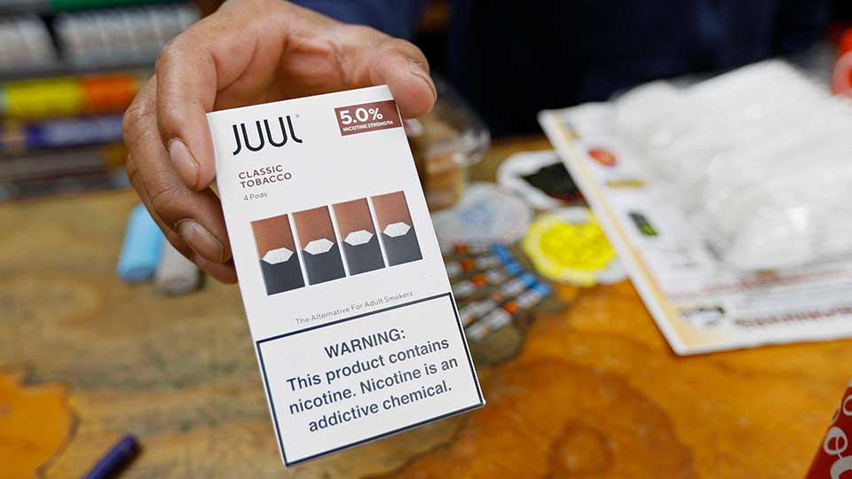 File - In this June 17, 2019, file photo, a cashier displays a packet of tobacco-flavored Juul pods at a store in San Francisco. Investigators from 39 states will look into the marketing and sales of vaping products by Juul Labs, including whether the company targeted youths and made misleading claims about nicotine content in its devices, officials announced Tuesday, Feb. 25, 2020. Juul released a statement saying it has halted television, print and digital advertising and eliminated most flavors in response to concerns by government officials and others.