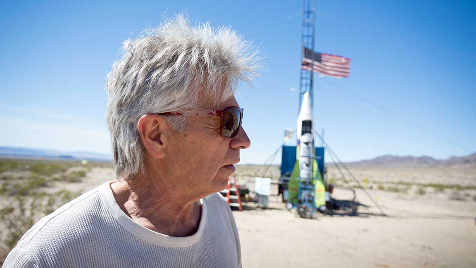 """FILE - In this March 6, 2018, file photo, """"Mad"""" Mike Hughes reacts after the decision to scrub another launch attempt of his rocket near Amboy, Calif. The self-taught rocket scientist who believes the Earth is flat propelled himself about 1,000 feet into the air before a hard-landing in the Mojave Desert that left him injured Saturday, March 24, 2018. Hughes tells The Associated Press that he injured his back but is otherwise fine after Saturday's launch near Amboy, Calif."""