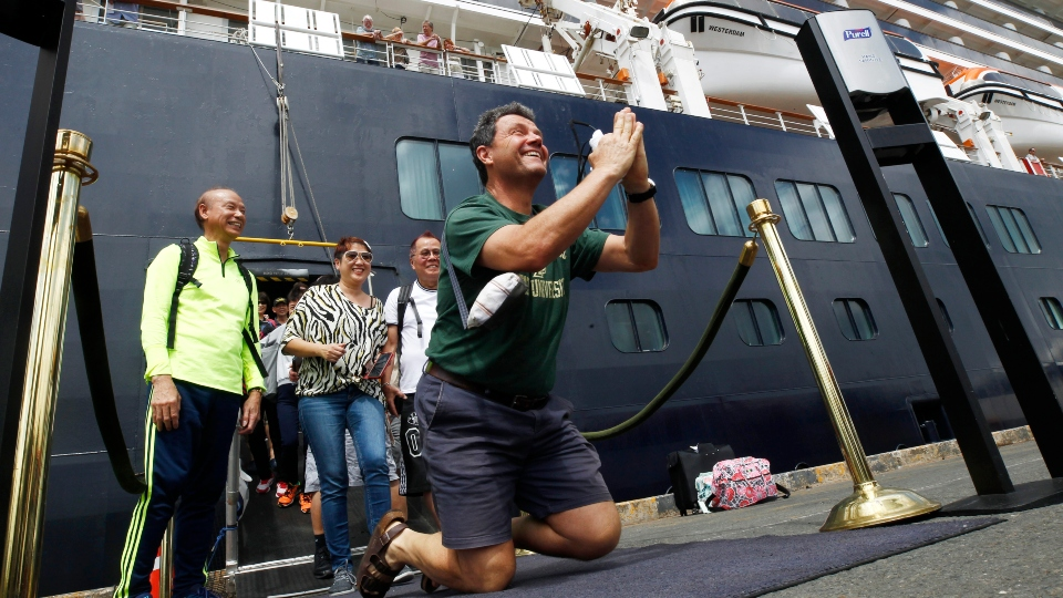 John Miller, from Orcas Island, Wash., reacts after he disembarked from the MS Westerdam, back, at the port of Sihanoukville, Cambodia.