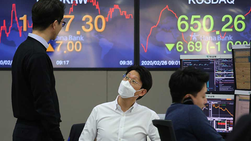 Currency traders work at the foreign exchange dealing room of the KEB Hana Bank headquarters in Seoul, South Korea, Wednesday, Feb. 26, 2020. Asian shares slid Wednesday following another sharp fall on Wall Street as fears spread that the growing virus outbreak will put the brakes on the global economy.
