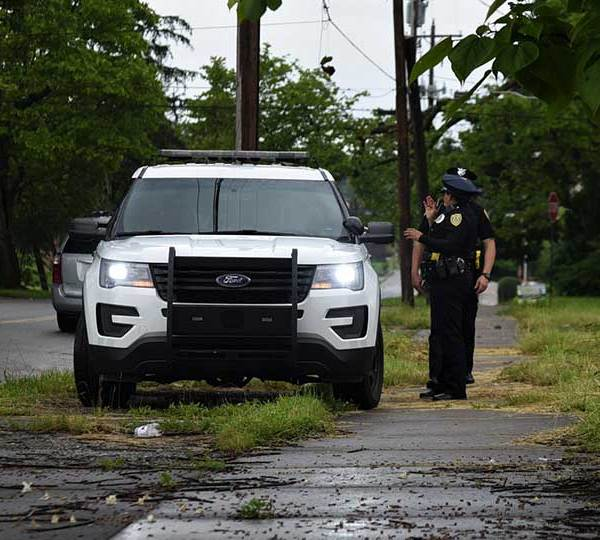 Youngstown police officers pause last June as they look for a robbery suspect on Southern Boulevard. The department answered over 62,000 calls in 2019, with over 21,000 of those calls on the South Side.