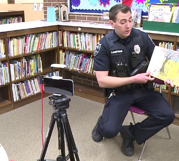 Canfield Officer Tim Lamping reading to students