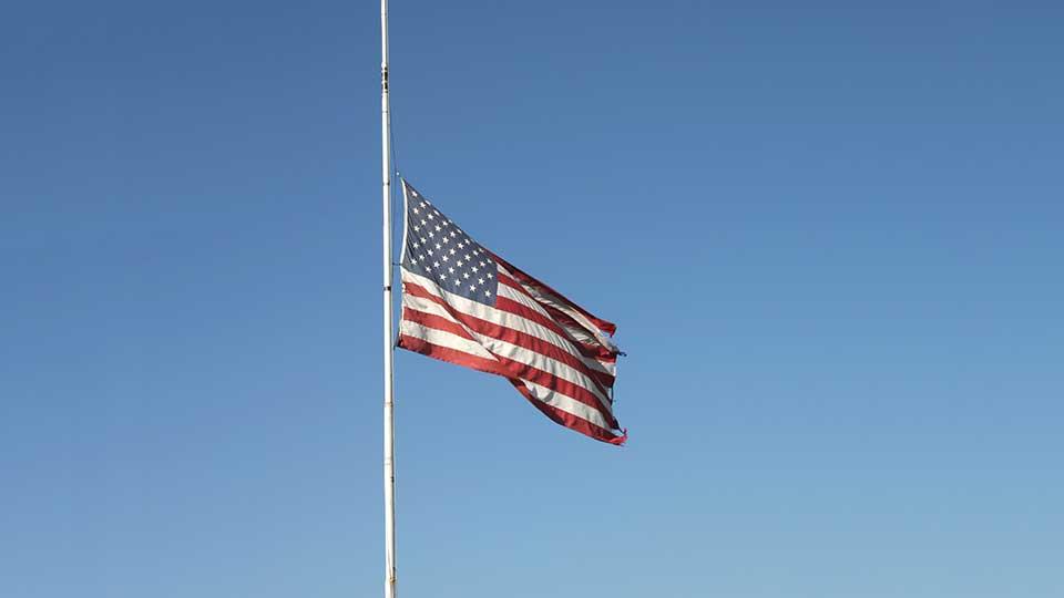 An American flag being flown at half staff.