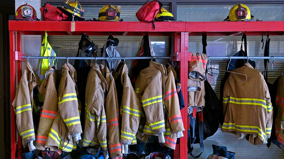 Firefighter gear hanging on a rack.