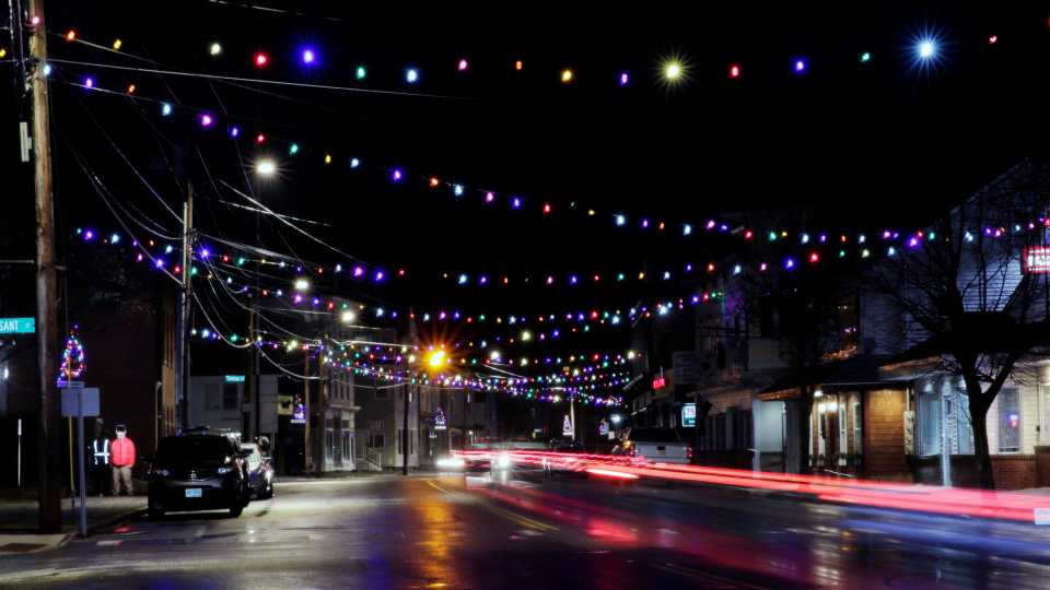 In this March 19, 2020, photo, car tail lights streak under Christmas lights recently turned back on in Farmington, N.H. As the coronavirus spreads, holiday lights are going back up to provide a bit of emotional and actual brightness.