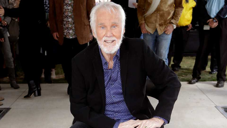 """FILE - In this Oct. 24, 2017 file photo, Kenny Rogers poses with his star on the Music City Walk of Fame in Nashville, Tenn. Actor-singer Kenny Rogers, the smooth, Grammy-winning balladeer who spanned jazz, folk, country and pop with such hits as """"Lucille,"""" """"Lady"""" and """"Islands in the Stream"""" and embraced his persona as """"The Gambler"""" on record and on TV died Friday night, March 20, 2020. He was 81."""