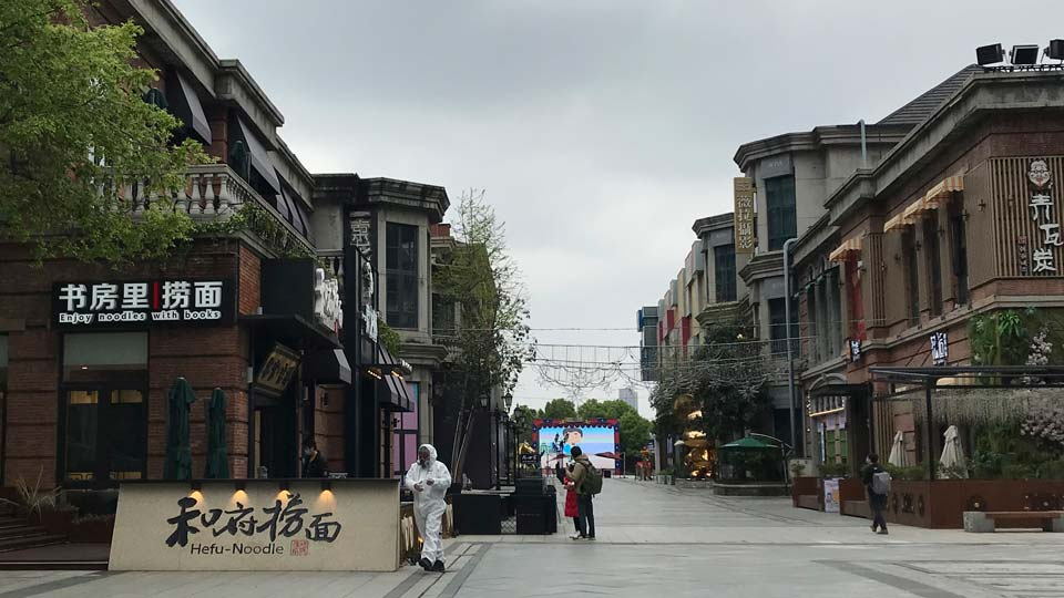 A store employee in a protectively suit waits for customers outside a re-opened retail street in Wuhan