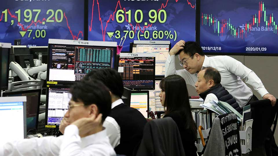 Currency traders watch monitors at the foreign exchange dealing room of the KEB Hana Bank headquarters in Seoul, South Korea, Tuesday, March 10, 2020. Shares edged slightly lower in Tokyo and Seoul after bouncing in and out of negative territory.