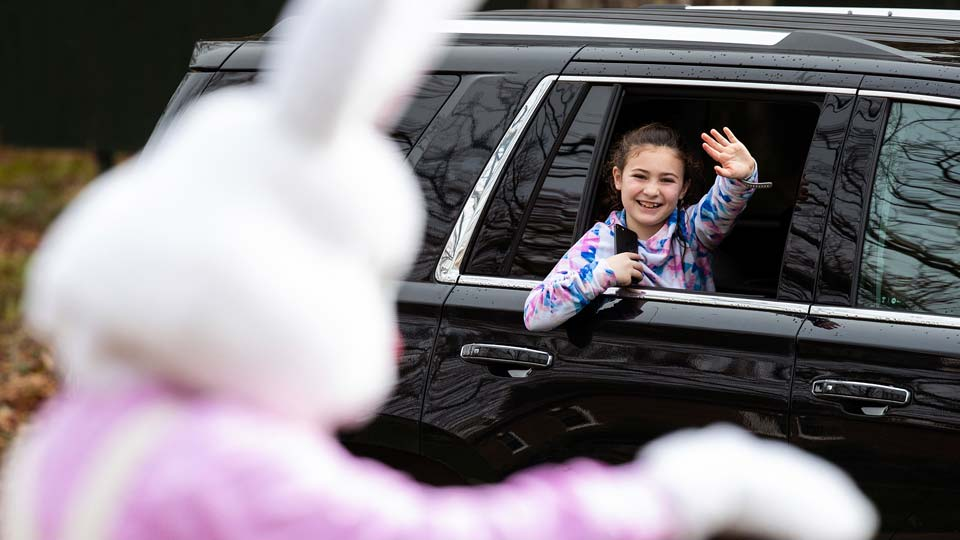 A girl waves to the Easter Bunny from her family's car