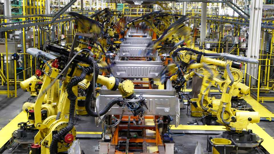 FILE - In this Sept. 27, 2018, file photo robots weld the bed of a 2018 Ford F-150 truck on the assembly line at the Ford Rouge assembly plant in Dearborn, Mich. U.S. businesses are edging their way toward figuring out how to bring their employees back to work amid the coronavirus pandemic, some more gracefully than others. Detroit-area automakers, which suspended production in March 2020, are now pushing to restart factories as soon as possible.