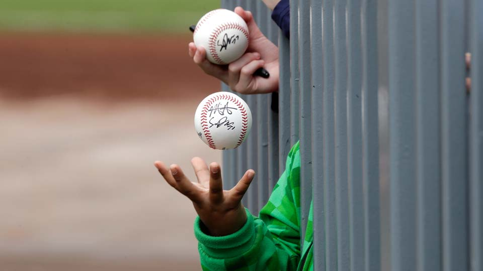 A child tosses an already-autographed baseball while awaiting another signature from a passing player before a spring training baseball game