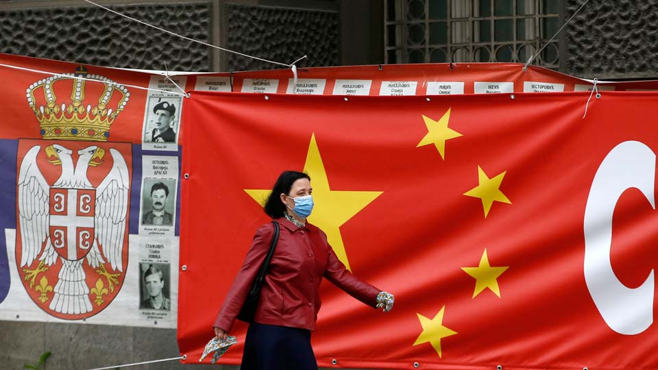 Chinese woman wearing a face mask walks by a Chinese flag