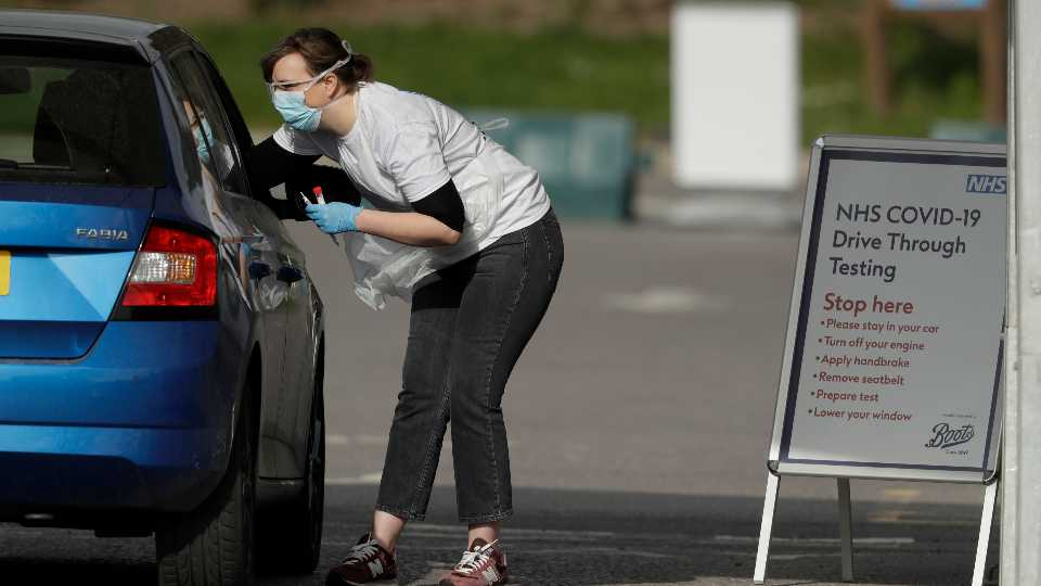 A NHS (National Health Service) worker is tested for Covid-19 at a drive-through testing centre in a car park at Chessington World of Adventures, Greater London, Saturday, April 4, 2020. The new coronavirus causes mild or moderate symptoms for most people, but for some, especially older adults and people with existing health problems, it can cause more severe illness or death. (