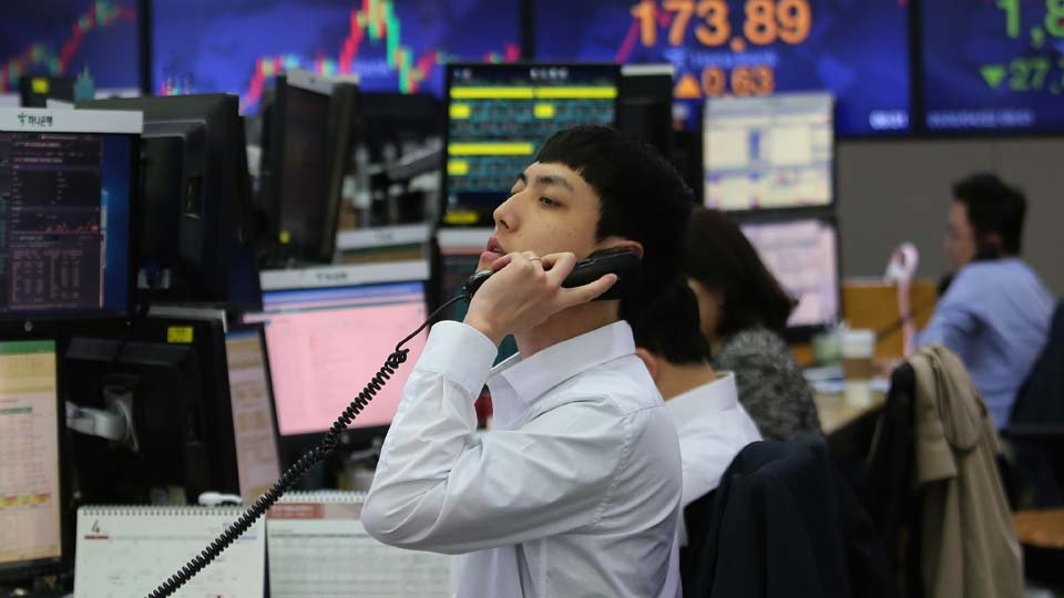 A currency trader talks on the phone at the foreign exchange dealing room of the KEB Hana Bank headquarters