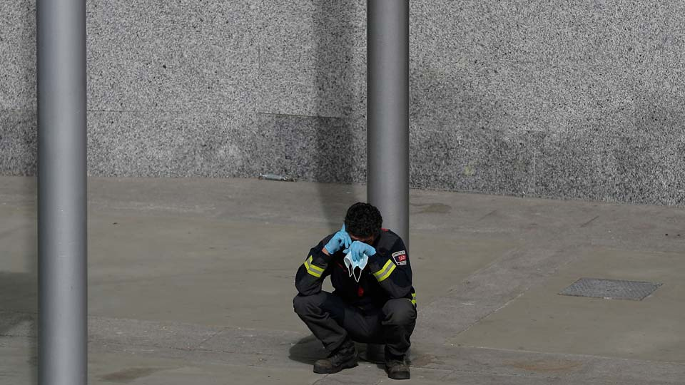 Firefighter talks on his phone as he rests at a temporary field hospital