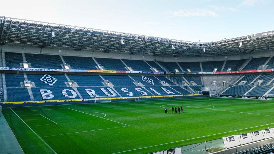Only a few workers stand on the pitch of the empty stadium of German Bundesliga soccer club Borussia Moenchengladbach