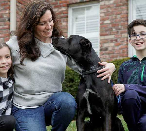 In this March 27, 2020 photo, Kim Simeon and children Annabel, 9, and Brennan, 11, pose for a photo with Nala, a dog they are fostering, in Omaha, Neb. The Simeon family was headed home to Omaha from a much-needed Smoky Mountains vacation when Kim Simeon spotted a social media post from the Nebraska Humane Society, pleading with people to consider fostering a pet