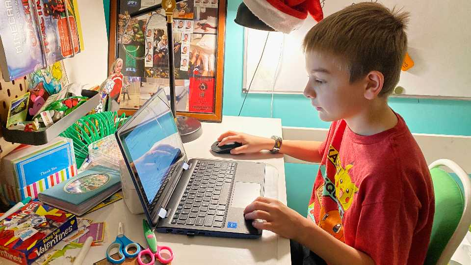 This April 9, 2020, photo released by Kara Illig shows her son, Eli Illig, 10, on his computer in Ebensburg, Pa. The frustration of parents is mounting as more families across the U.S. enter their second or even third week of total distance learning, and some say it will be their last.
