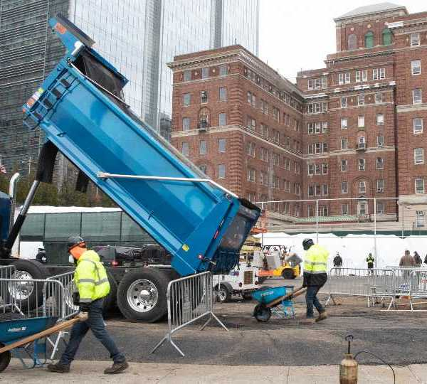 Construction workers are seen at the site of a makeshift morgue being built in New York, Wednesday, March 25, 2020. New York officials are keeping a close eye on already-stressed hospitals as the number of cases is projected to rise for perhaps three more weeks.The new coronavirus causes mild or moderate symptoms for most people, but for some, especially older adults and people with existing health problems, it can cause more severe illness or death.