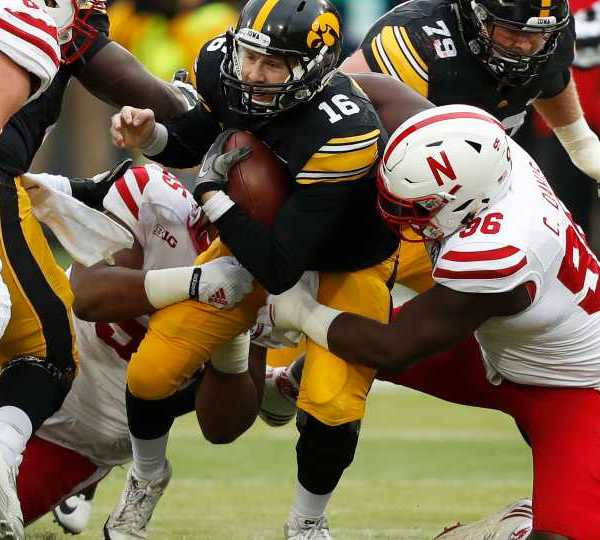 Iowa quarterback C.J. Beathard (16) is sacked by Nebraska defensive tackle Carlos Davis, right, during the first half of an NCAA college football game, Friday, Nov. 25, 2016, in Iowa City, Iowa.