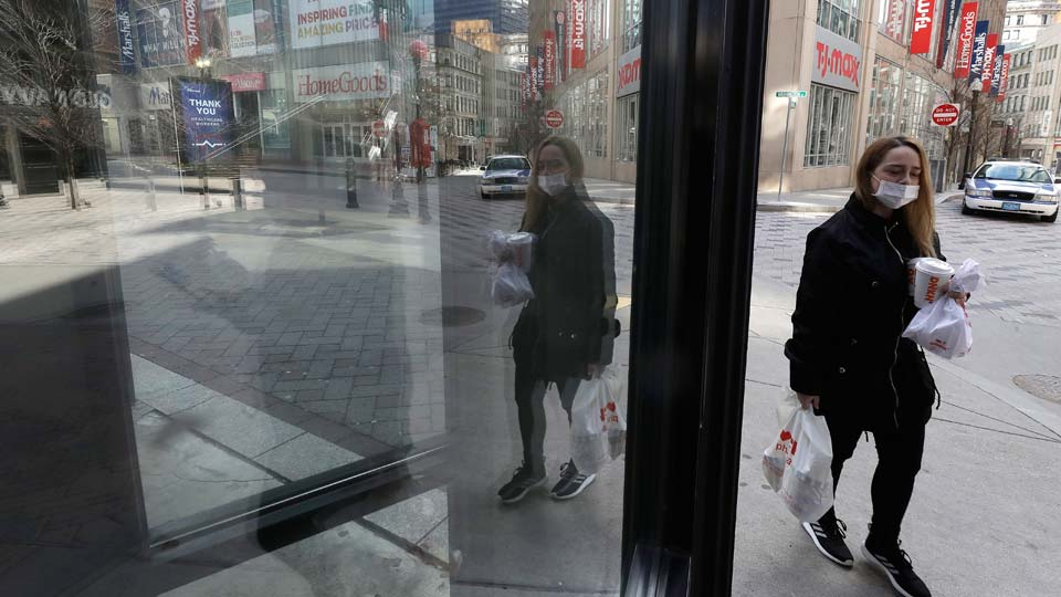 A passerby walks past an entrance to a closed store in the nearly empty Downtown Crossing neighborhood