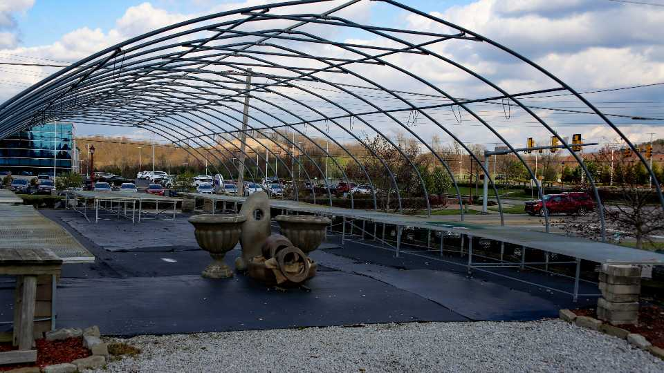 """Empty tables for garden plants are under the framework for a greenhouse, Friday, April 24, 2020, in Cranberry Township. Some garden centers remain shuttered under Wolf's statewide March 19 order for """"non-life-sustaining"""" businesses to close. Nurseries and greenhouses are allowed to remain open and selling, while garden center owners complain that big-box stores, farming supply stores or competitors that sell farm supplies, building materials or other qualifying goods can stay open and sell gardening supplies."""