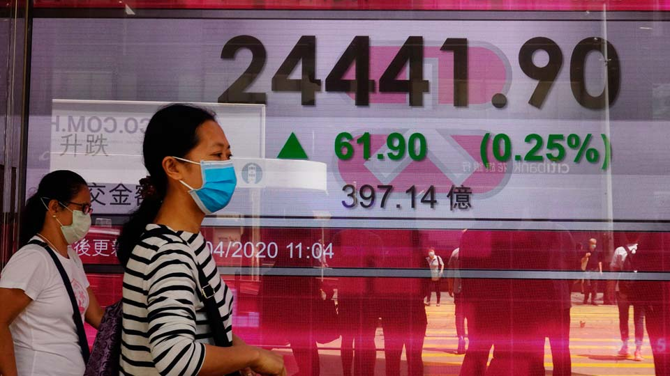People wearing face masks walk past a bank electronic board showing the Hong Kong share index at Hong Kong Stock Exchange Monday, April 20, 2020