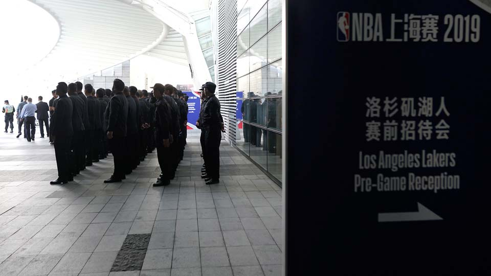 Security personnel stand in formation near a promotion board for an NBA preseason game to be held at the Mercedes Benz Arena in Shanghai, China