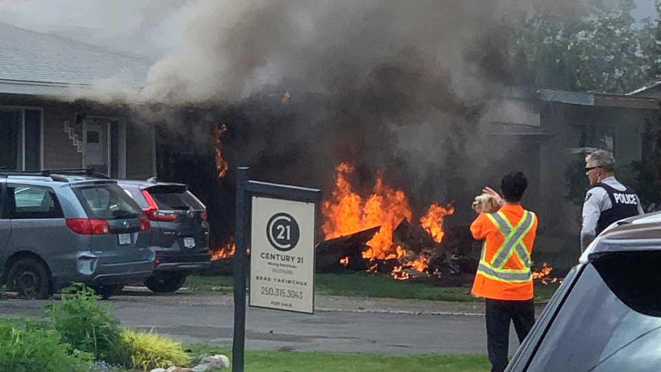 This photo provided by Elwood Delaney shows the scene of a crash involving a Canadian Forces Snowbirds airplane in Kamloops, Canada, Sunday, May 17, 2020. A Canadian acrobatic jet has crashed into the British Columbia neighborhood during a flyover intended to boost morale during the pandemic, killing at least one crew member and setting the house on fire.
