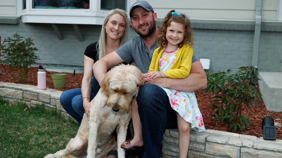 Eli Oderberg, center, sits with Katie Evers, left, their 4-year-old daughter, Everlee, and the couple's goldendoodle outside their home in southeast Denver