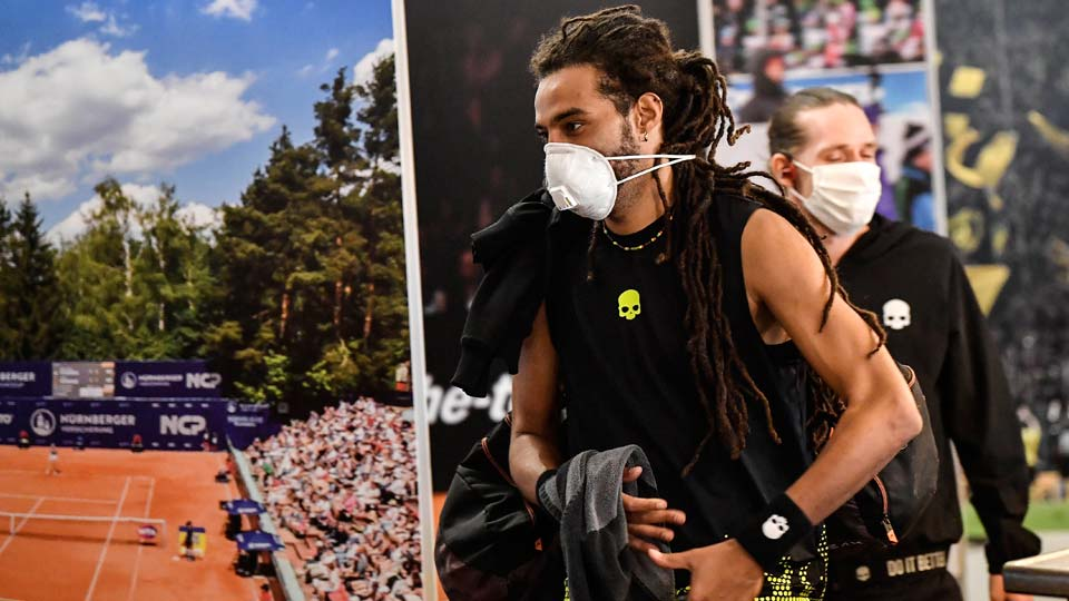Germany's tennis player Dustin Brown wears a face mask as he walks by a poster at a pro-tennis tournament