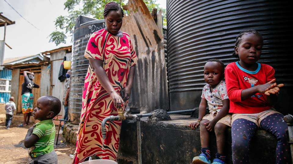 Judith Andeka a widow and mother of five, fetches water with a bucket in the Kibera slum, or informal settlement, of Nairobi, Kenya
