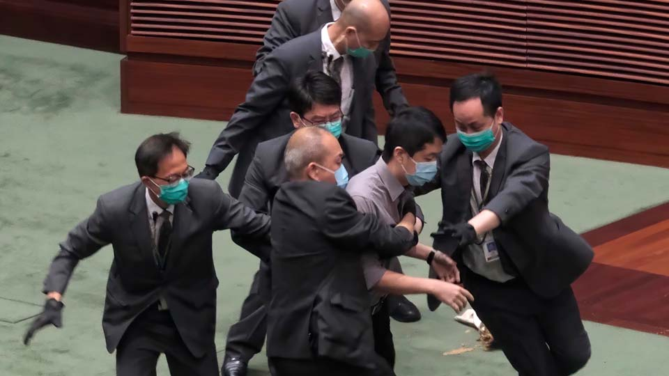 Pro-democracy lawmaker Ted Hui, center, struggles with security personnel at the main chamber of the Legislative Council