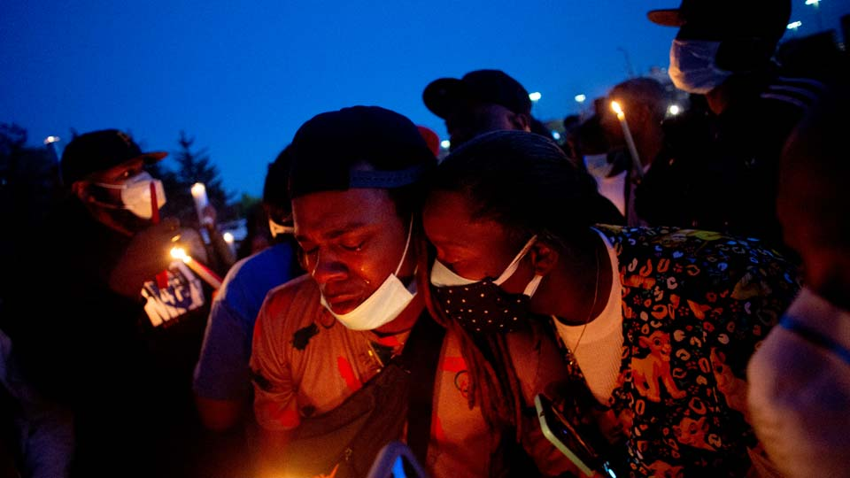 Maalik Mitchell, center left, sheds tears as he says goodbye to his father, Calvin Munerlyn, during a vigil Sunday, May 3, 2020, in Flint, Mich. Munerlyn was shot and killed Friday at a Family Dollar store in Flint