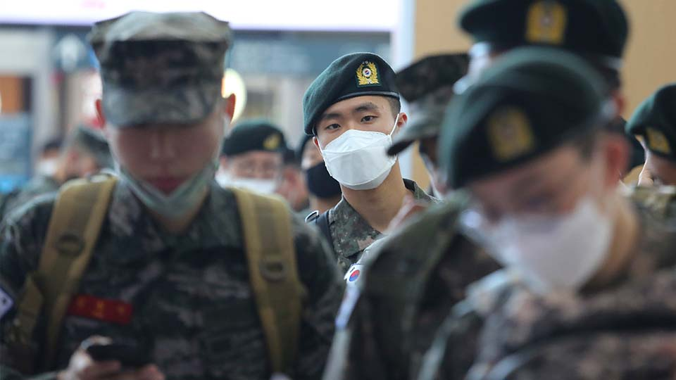 Military soldiers wearing face masks line up to buy train tickets as they are allowed to go on leave after more than two months