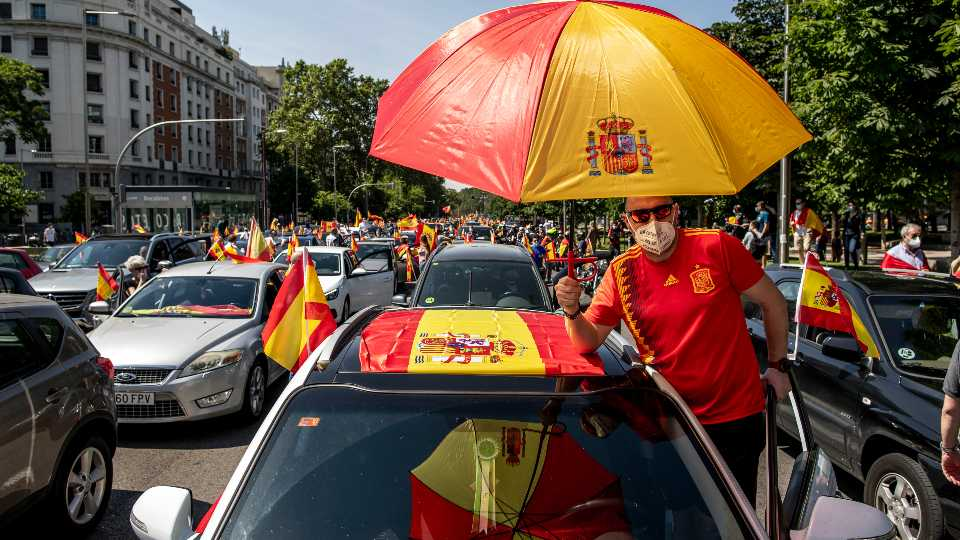 People wave Spanish flags during a drive-in protest organised by Spain's far-right Vox party against the Spanish government's handling of the nation's coronavirus outbreak in Madrid, Spain Saturday, May 23, 2020.
