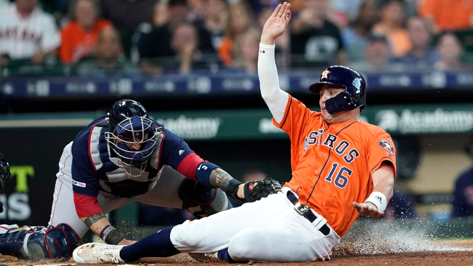 Houston Astros' Aledmys Diaz (16) scoring as Boston Red Sox catcher Sandy Leon reaches to tag him at home plate during the second inning of a baseball game in Houston.