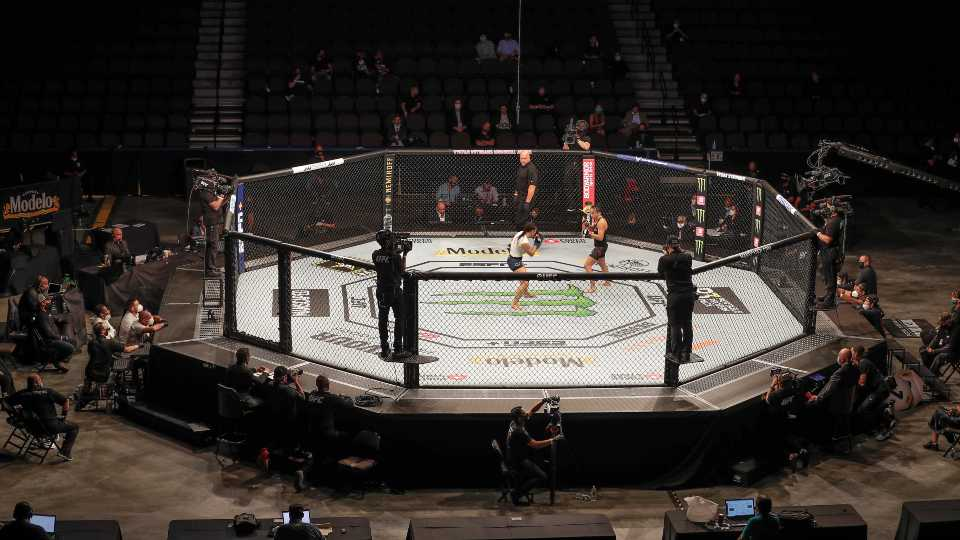 Michelle Waterson, center left, and Carla Esparza battle without spectators during a UFC 249 mixed martial arts bout, Saturday, May 9, 2020, in Jacksonville, Fla.