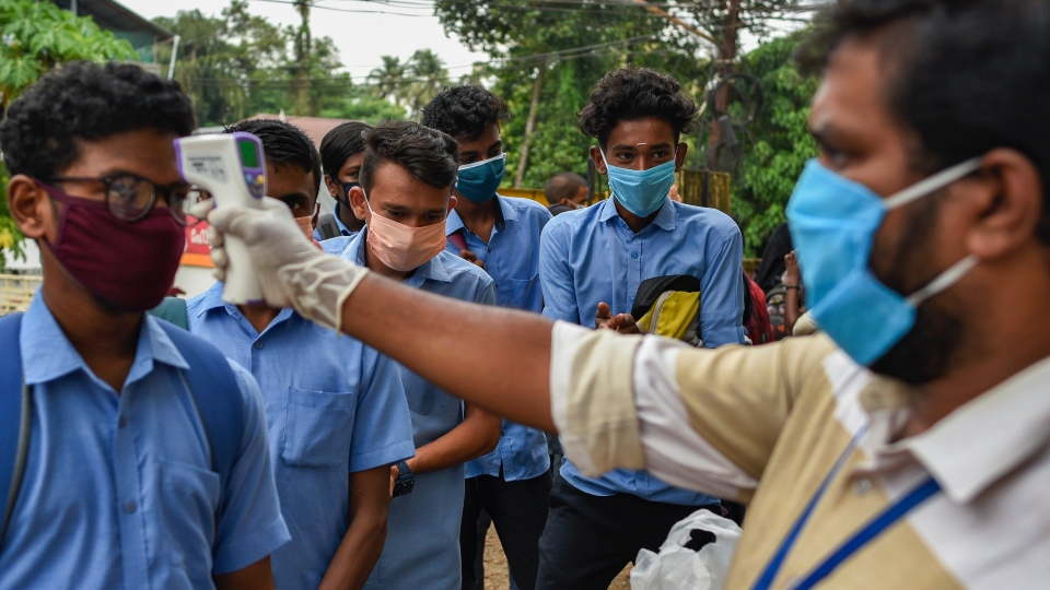 School children wearing masks get their hands sanitized and temperatures checked as they arrive to appear for state board examination during the coronavirus pandemic in Kochi.