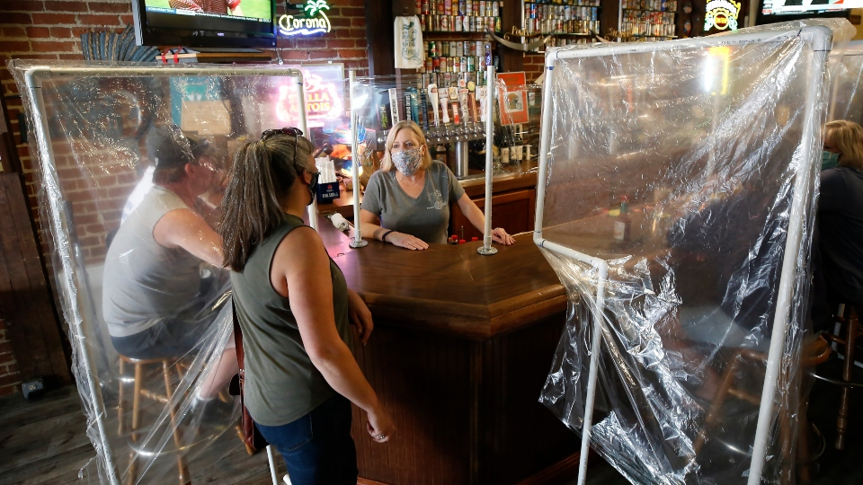Sheila Kelly, owner of Powell's Steamer Co. & Pub, center, stands behind makeshift barriers as she helps patrons at her restaurant in the El Dorado County town of Placerville, Calif.