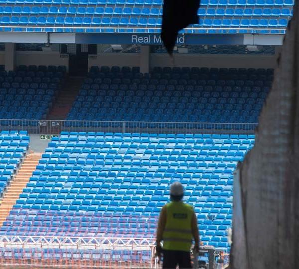 Workers walk into Real Madrid's Santiago Bernabeu stadium