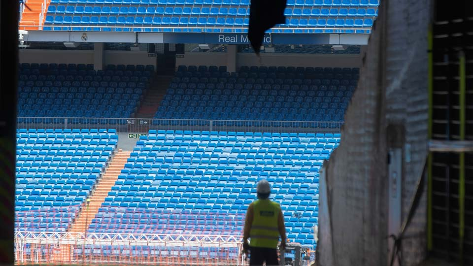 Workers walk into Real Madrid's Santiago Bernabeu stadium