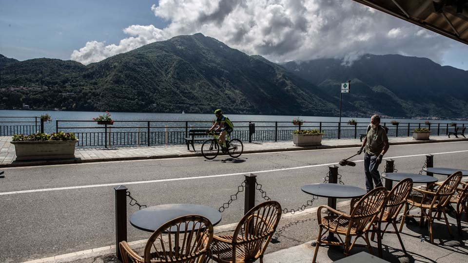 A worker walks holding a lawn mower as a biker rides past a cafe outdoor tables in Tremezzo, Lake Como, Italy