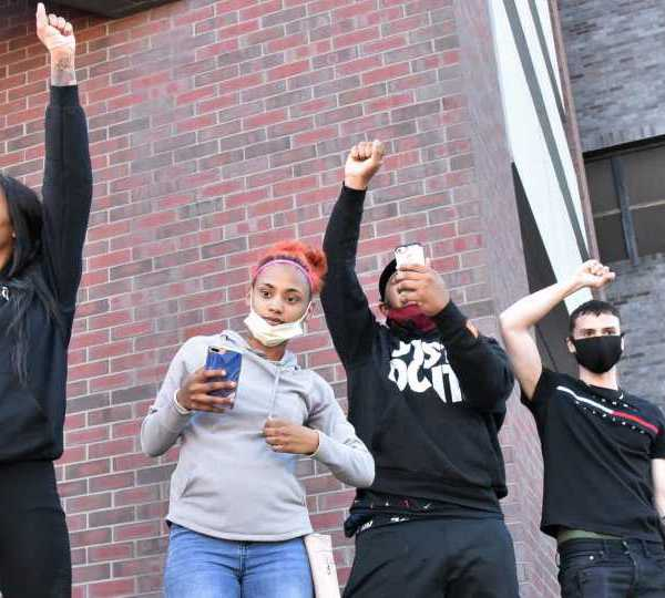 Protesters raise their fists to crowd
